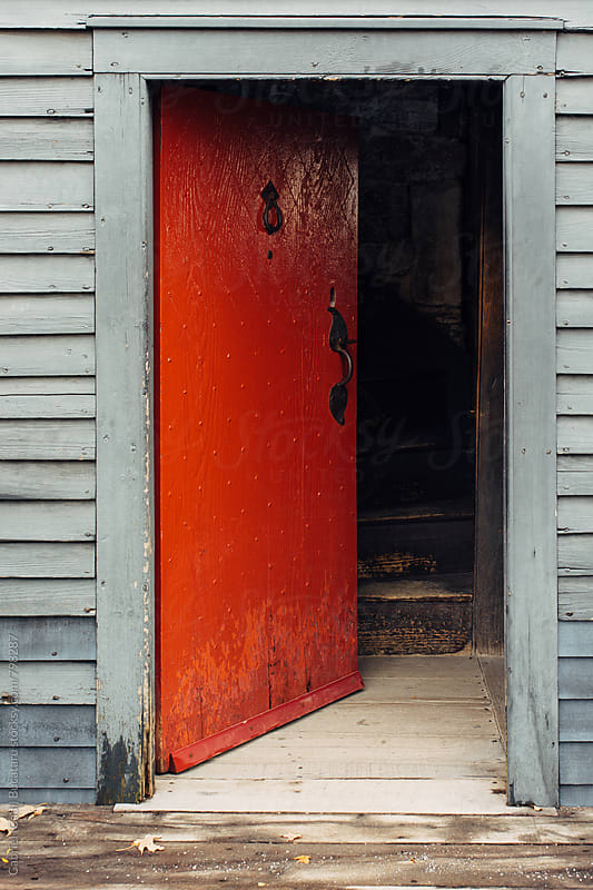 Open red door at a rustic house by Gabriel (Gabi) Bucataru for Stocksy United
