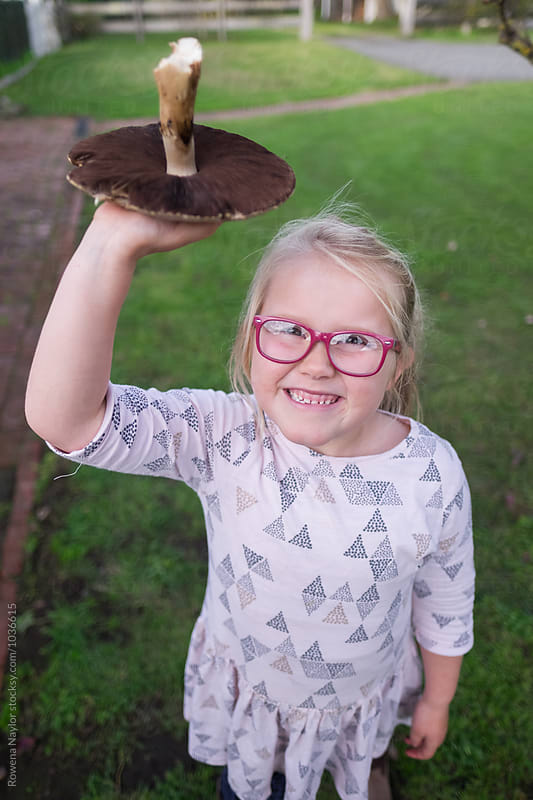 Little girl holding a giant mushroom by Rowena Naylor for Stocksy United
