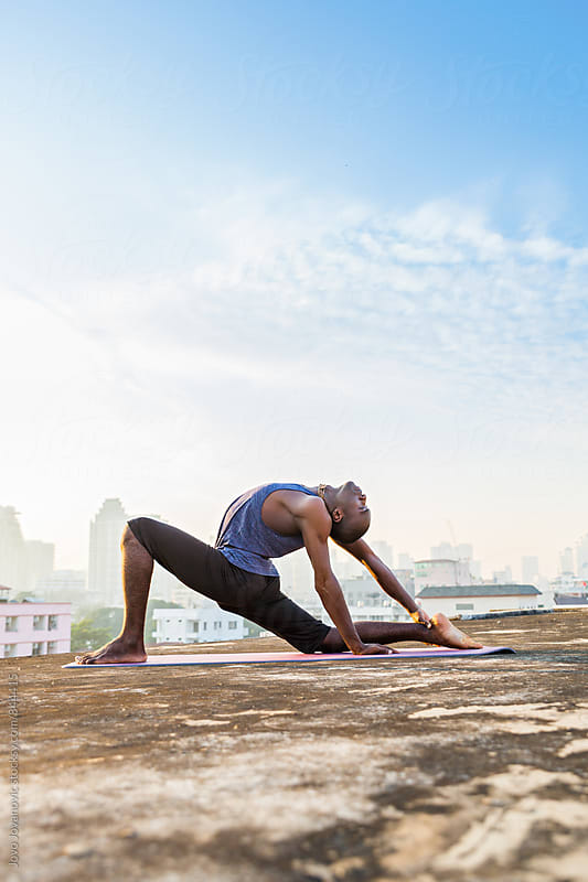 Vertical shot of a handsome dark skinned man practicing yoga on a city rooftop  by Jovo Jovanovic for Stocksy United