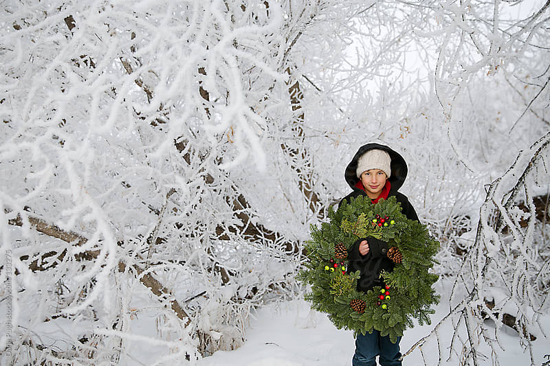 Boy with Christmas wreath by Dana Pugh for Stocksy United