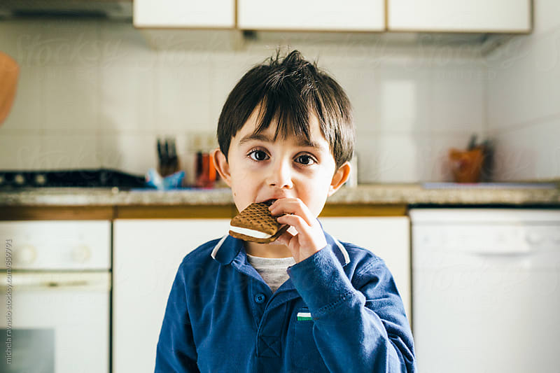 A satisfied child eats his cookie ice cream by michela ravasio for Stocksy United