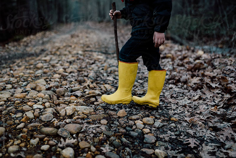 child wearing yellow boots on a walk by Léa Jones for Stocksy United