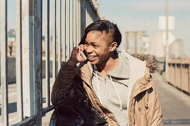 Girl on the phone on the Brooklyn Bridge in New York City  by Cameron Whitman for Stocksy United