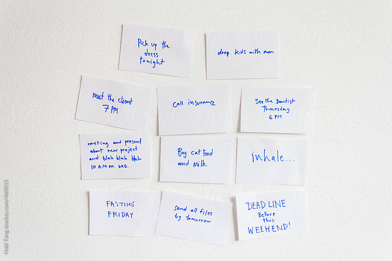 White paper note for reminging written with blue ink on the white wall by Nabi Tang for Stocksy United