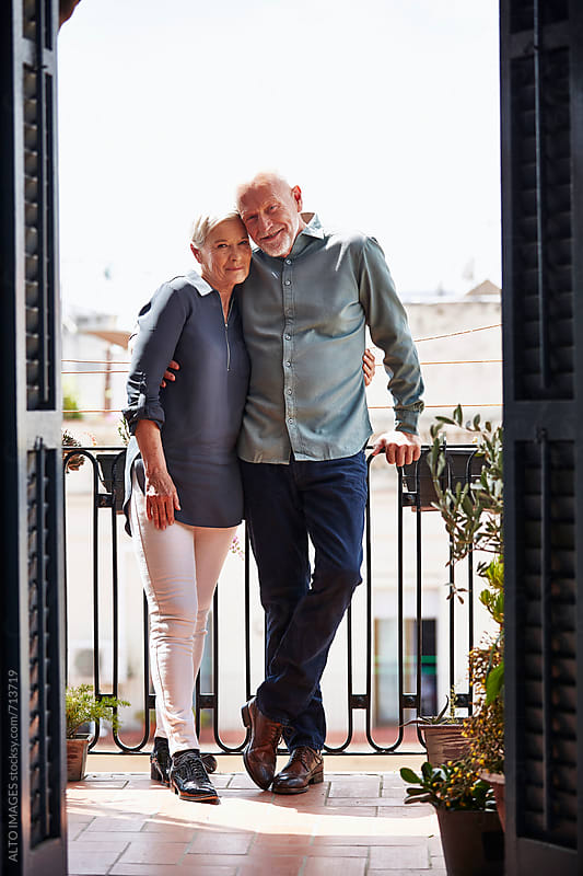 Loving Senior Couple Standing On Balcony by ALTO IMAGES for Stocksy United