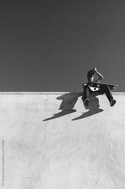 Skateboarder resting on half pipe wall by Urs Siedentop & Co for Stocksy United