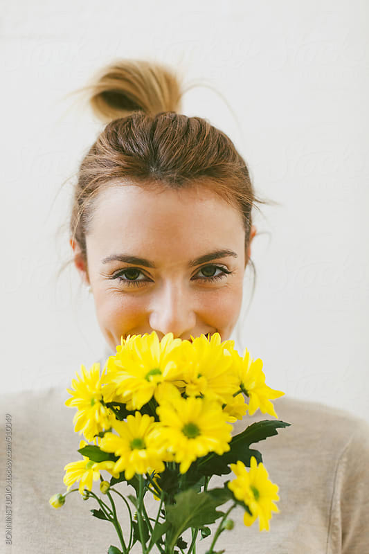 Portrait of happy young woman holding a bouquet of yellow flowers. by BONNINSTUDIO for Stocksy United