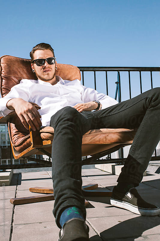 Cool guy with hip sunglasses sitting in a chair. by Koen Meershoek for Stocksy United