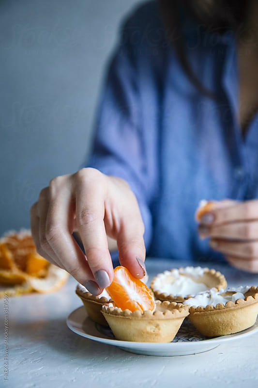 Close-up of four tarts with white cream and tangerine by Danil Nevsky for Stocksy United