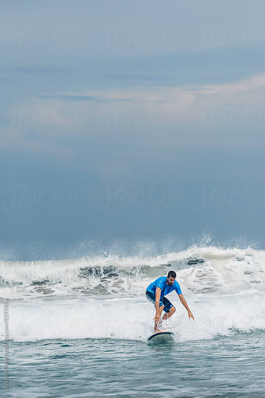 Young man learning to surf the waves on long surfboard by Jovana Milanko for Stocksy United