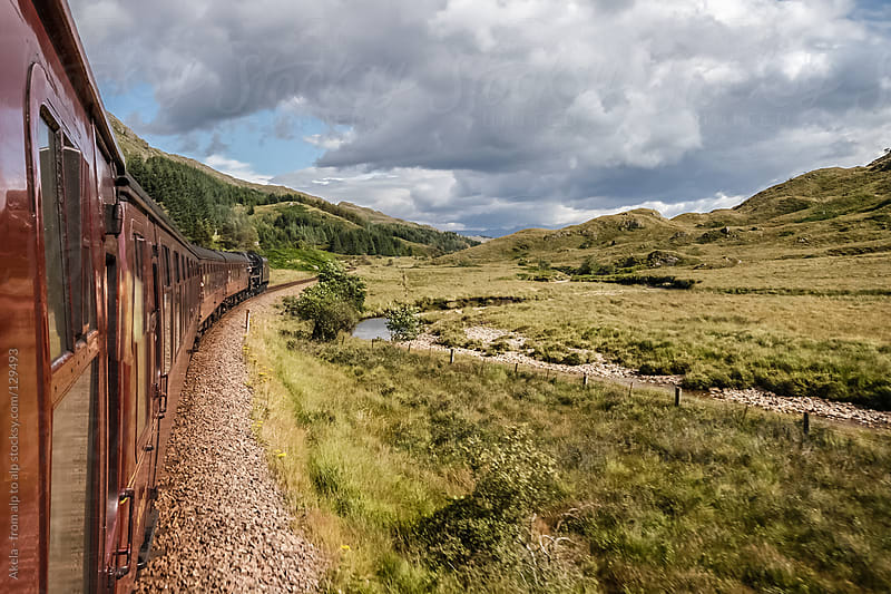 train is passing through scottish highlands by Leander Nardin for Stocksy United