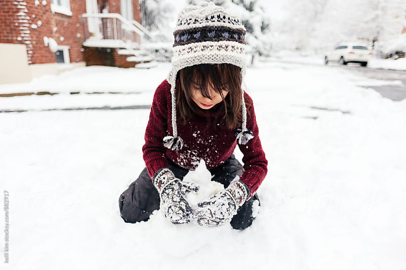 Young Mixed Race Boy Plays in Snow Outside by kelli kim for Stocksy United