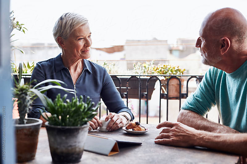 Senior Woman Having Breakfast With Man On Balcony by ALTO IMAGES for Stocksy United