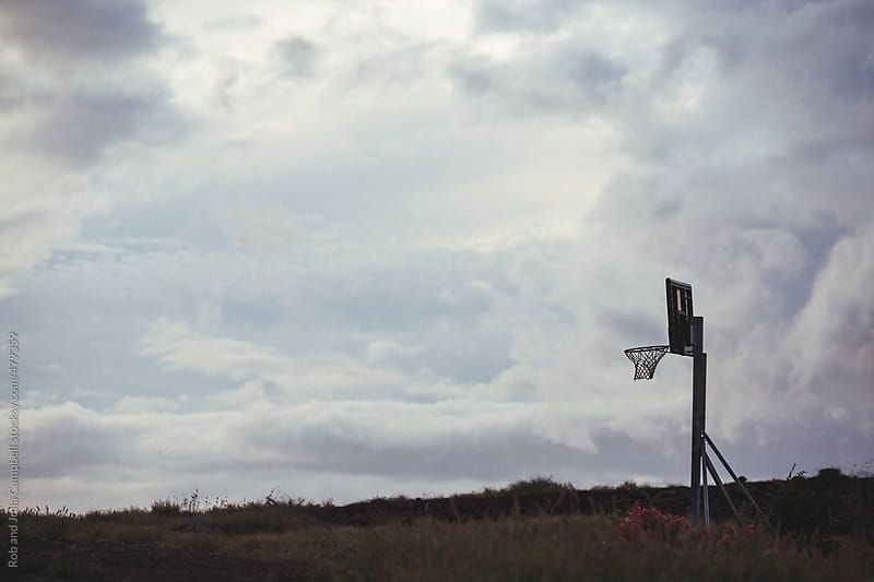 Silhouette of outdoor basketball hoop on clouds and sky by Rob and Julia Campbell for Stocksy United