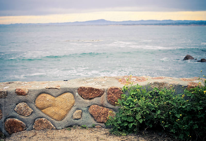 Wall with a big heart rock in the middle by Carolyn Lagattuta for Stocksy United
