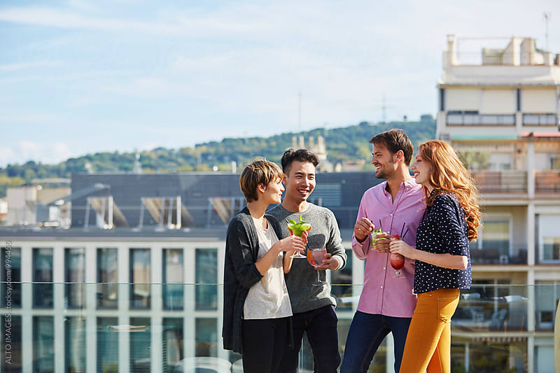 Happy Friends Enjoying Drinks On Hotel Terrace by ALTO IMAGES for Stocksy United