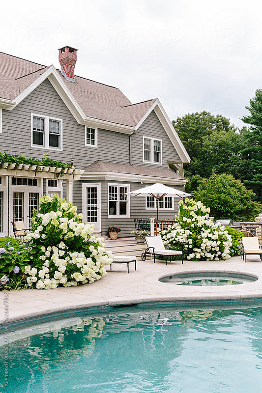 Luxury Home   with Summer flowers and hot tub by Raymond Forbes LLC for Stocksy United
