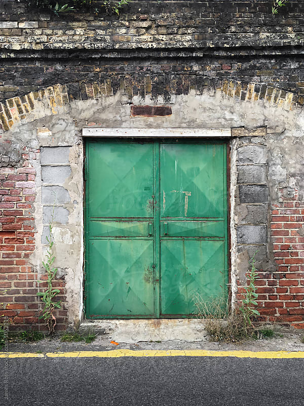 Green steel door by James Ross for Stocksy United