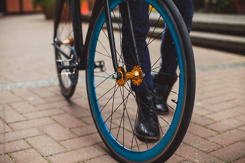 Man with black boots walks his bike. by Cherish Bryck for Stocksy United