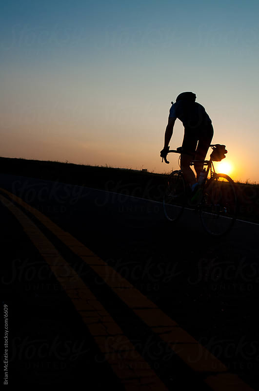 Solo Cyclist vs the Setting Sun by Brian McEntire for Stocksy United
