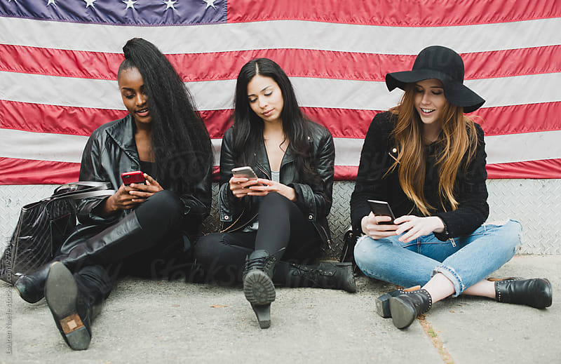 Young women on cell phones by American flag by Lauren Naefe for Stocksy United