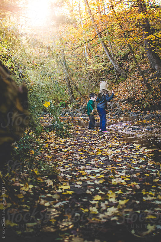 Two kids outside by a creek by Lindsay Crandall for Stocksy United