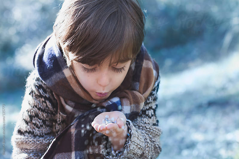 Boy blowing glitters from his hand in Winter by Beatrix Boros for Stocksy United