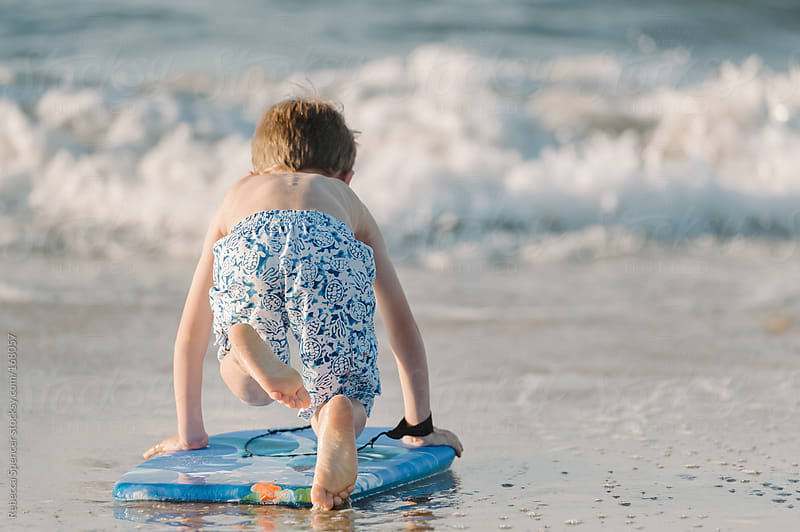 Boy facing waves on surf board by Rebecca Spencer for Stocksy United