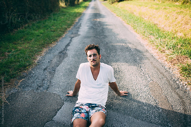 man sitting on the road by Thais Ramos Varela for Stocksy United