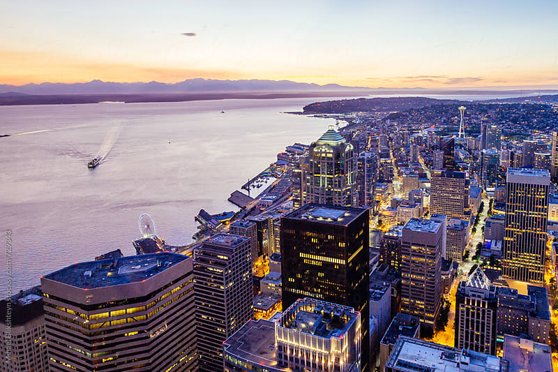 Aerial view of downtown Seattle with Space Needle, Washington State ferry and Pugest Sound at sunset by Mihael Blikshteyn for Stocksy United