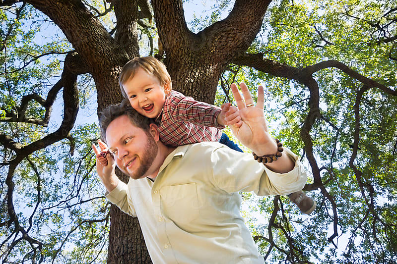Happy son and father, riding piggyback under a tree by yuko hirao for Stocksy United