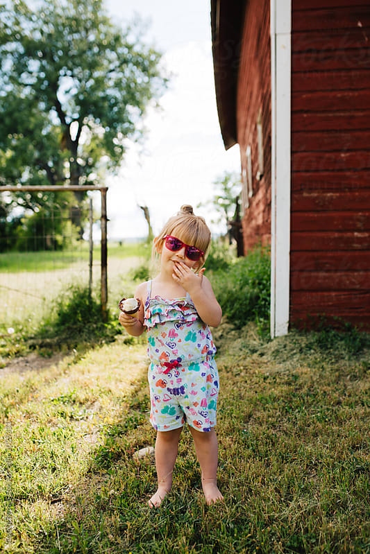 Toddler girl eating an ice cream cone by Jessica Byrum for Stocksy United