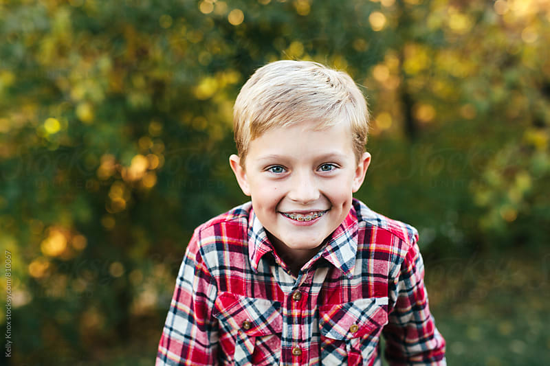 autumn portrait of a happy boy by Kelly Knox for Stocksy United