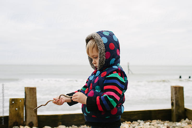 Child examines driftwood on a beach in winter. by Julia Forsman for Stocksy United
