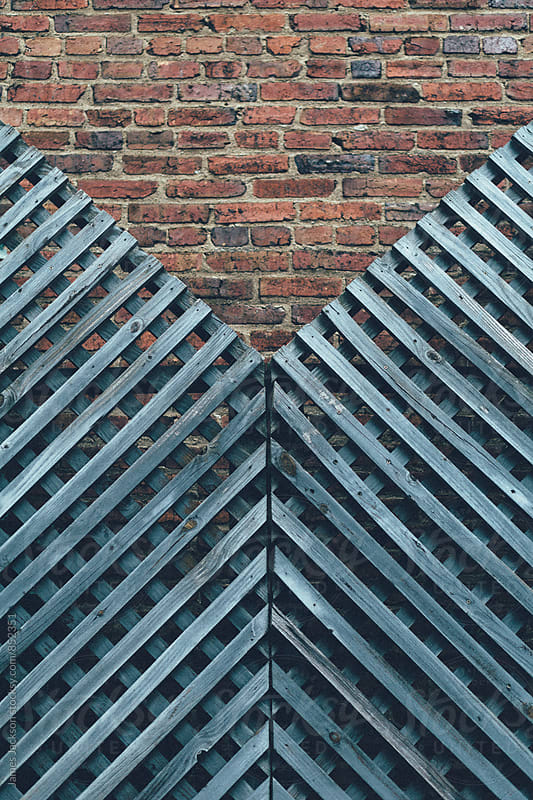 Weathered unpainted lattice and brick geometry by James Jackson for Stocksy United