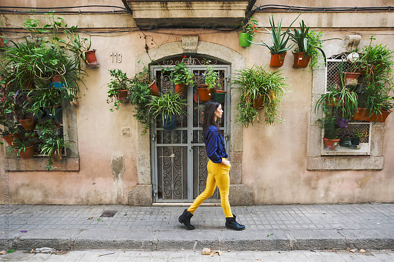 Woman walking in front a house with a lot of plants hanging. La Barceloneta, Barcelona. by BONNINSTUDIO for Stocksy United