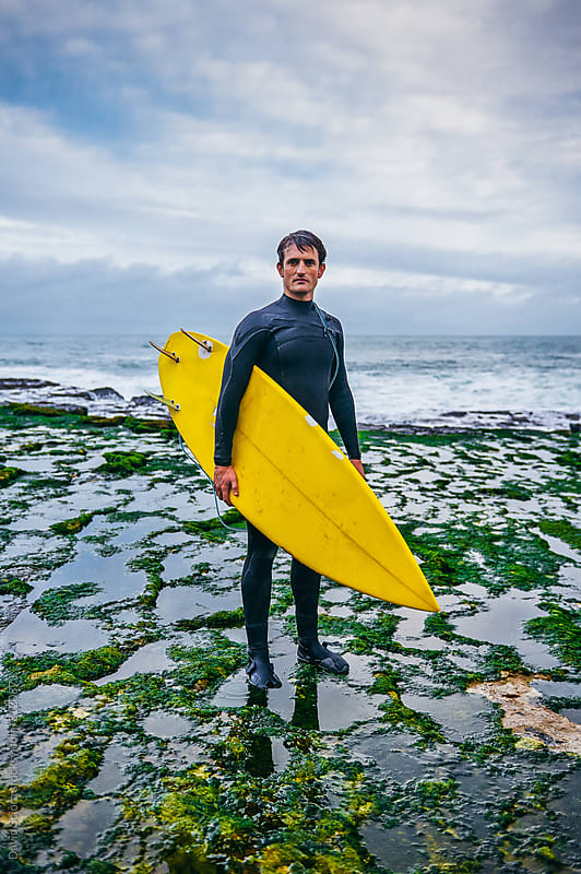 Portrait of a surfer on a beach by David Sciora for Stocksy United