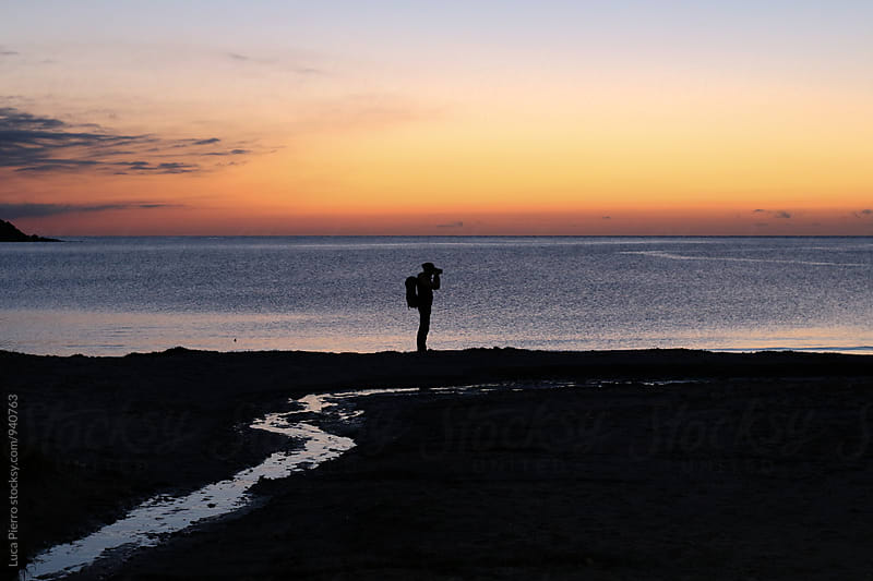 Photographer taking a picture at the sunrise by Luca Pierro for Stocksy United