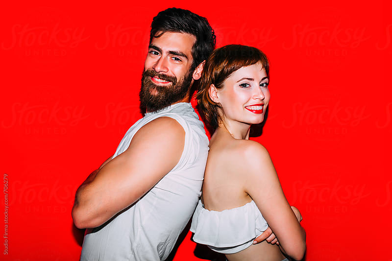 Young love couple having fun in front of the red background. by Studio Firma for Stocksy United