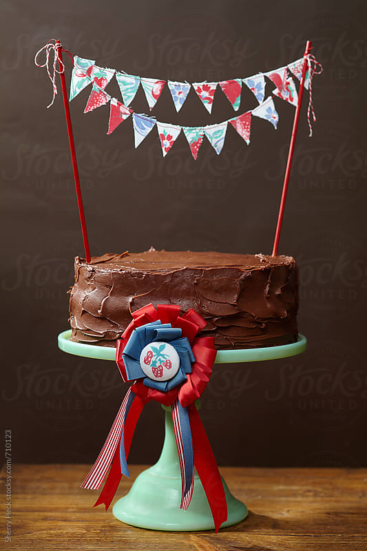 Chocolate cake on green cake stand with DIY bunting banner by Sherry Heck for Stocksy United