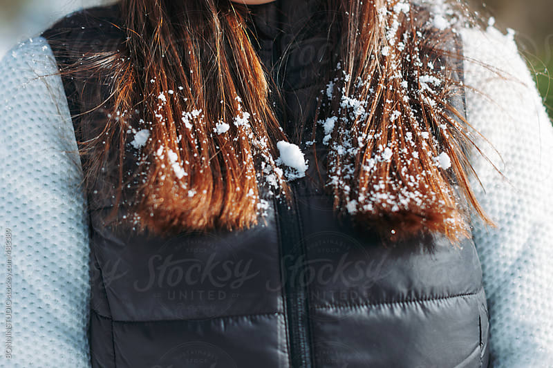 Closeup of a young woman with snow in her hair.  by BONNINSTUDIO for Stocksy United