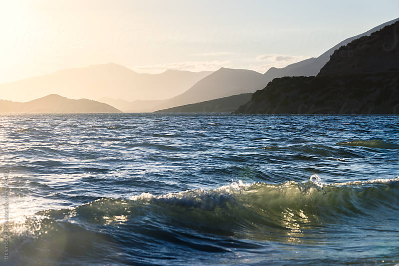 Crashing Waves with Mountains at Sunset by Helen Sotiriadis for Stocksy United
