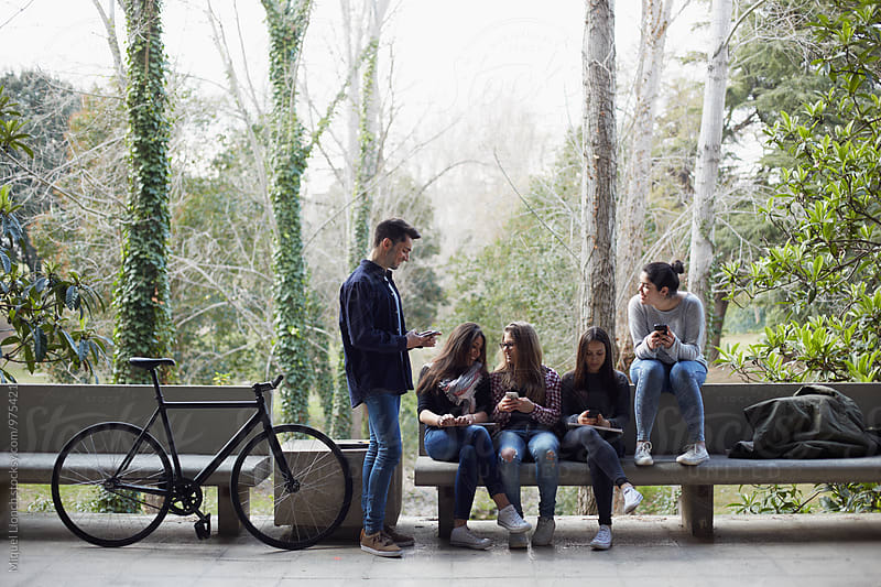 Group of young people talking in a relaxed moment in the university campus by Miquel Llonch for Stocksy United