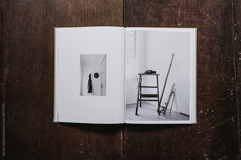 book open to page of photo from minimal cabin by Nicole Mason for Stocksy United