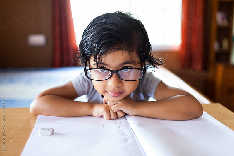 Little girl with glasses resting her head on a notebook by Saptak Ganguly for Stocksy United