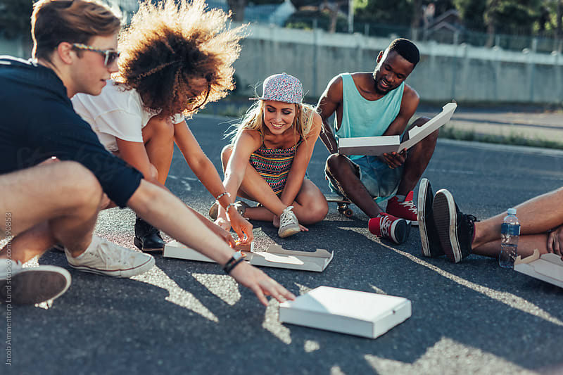 Group of young friends eating pizza outdoors by Jacob Ammentorp Lund for Stocksy United