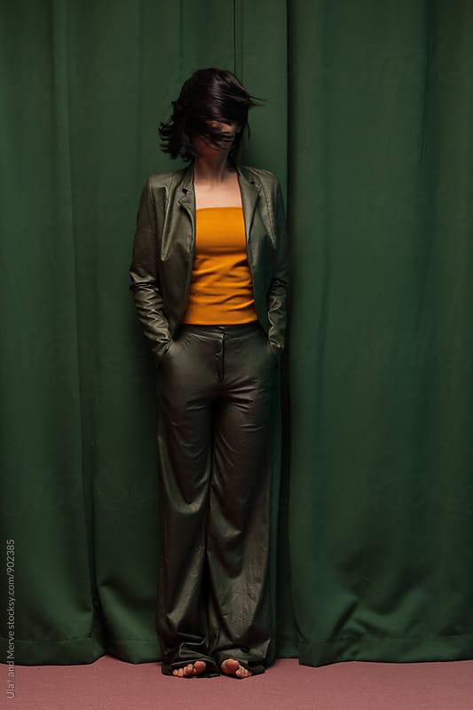 young brunette wearing a green faux leather suit and moving her head by Ulaş and Merve for Stocksy United