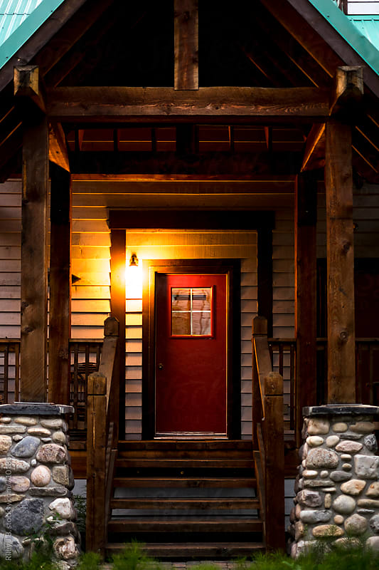 Porch and red door of a rustic cabin by Riley J.B. for Stocksy United