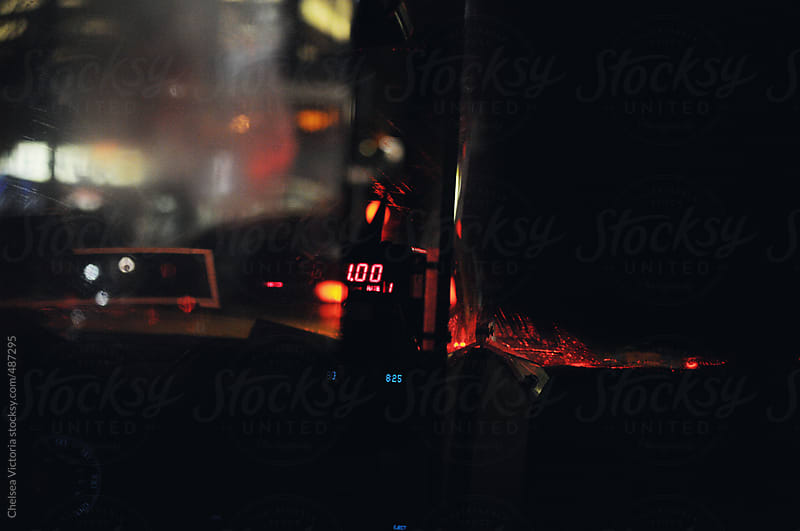 The inside of a taxi cab at night in Manhattan by Chelsea Victoria for Stocksy United