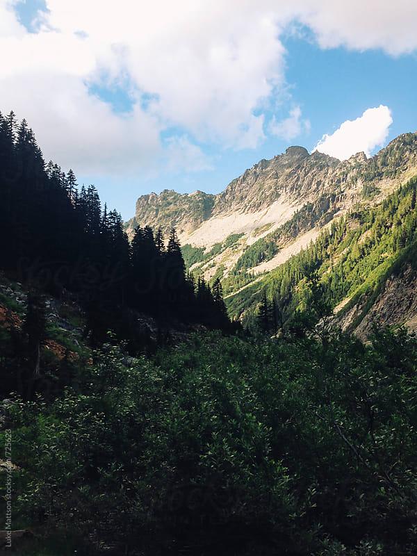View Of Mountains From Dark Hillside by Luke Mattson for Stocksy United